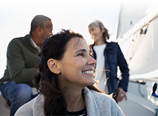 Woman on boat smiling and looking out towards ocean