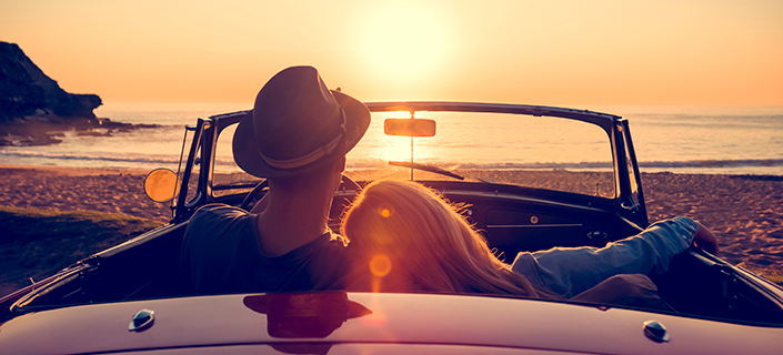 Couple enjoying a sunset at the beach while sitting in a convertible sports car