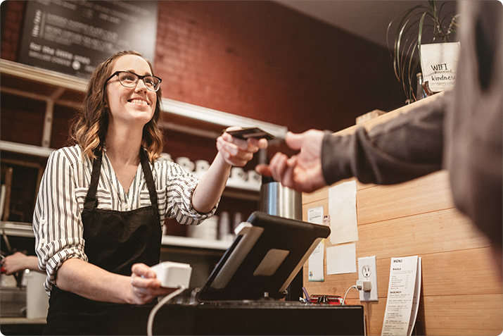 Happy cashier hands back an EMV chip card