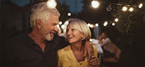 Older couple embracing and smiling in backyard celebration