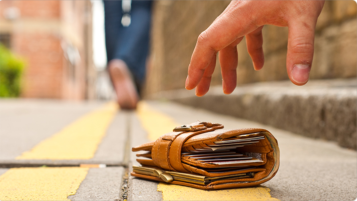 A man picks up a wallet in the road
