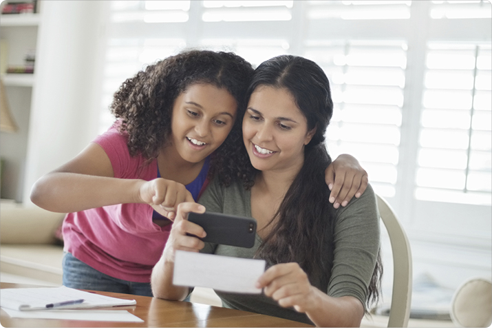Mom and daughter deposit a check on a mobile device.