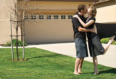 Couple kissing in front of their FHA house
